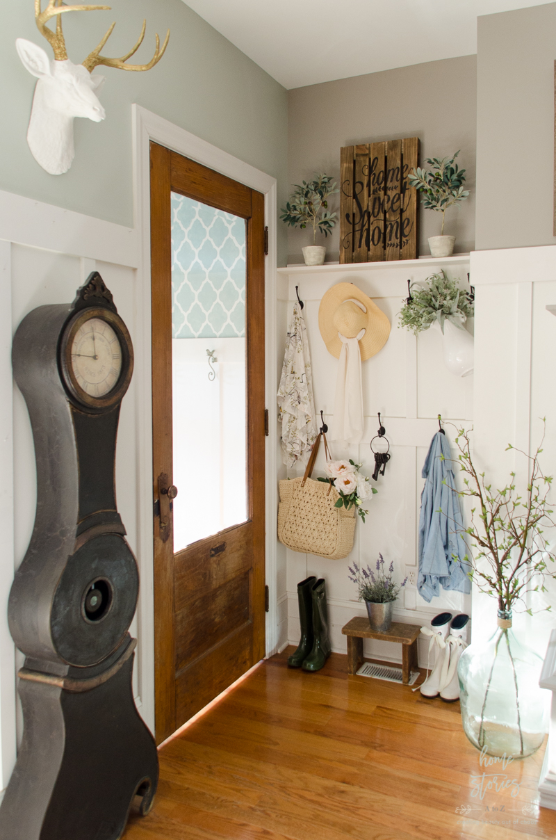 A White Farmhouse Pitcher Filled With Greenery And Straw Bag Faux Flowers Adds Whimsical Touch Of Spring To The Space